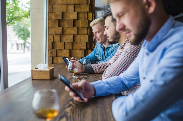 Row of male friends using their mobiles in the restaurant