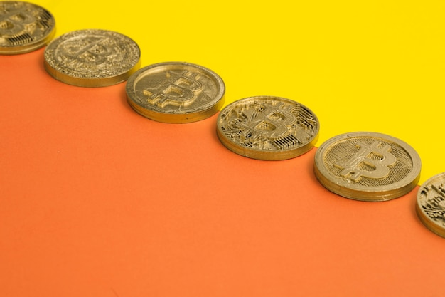 Row of many bitcoins over the yellow and an orange dual background