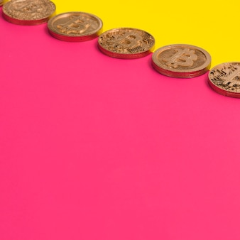 Row of many bitcoins over the yellow and pink dual background