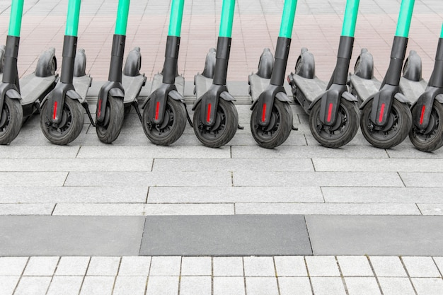 Row of many electric scooters standing on pavement.