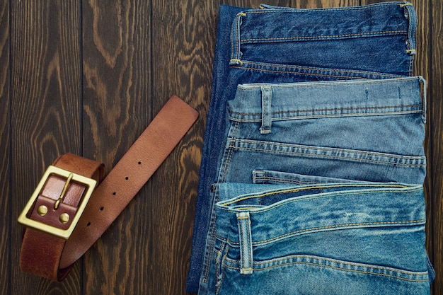 Row of mens jeans and leather belt on wooden background, top view
