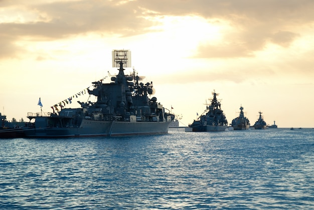 Row of military ships against marine sunset