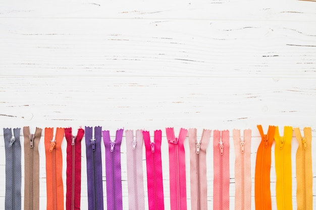 Row of multi colored zippers on wooden background
