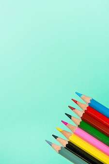 Row of multicolored pencils crayons on turquoise background