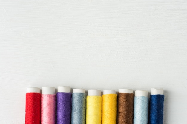 Row of multicolored sewing threads on cardboard spools. white wood background.