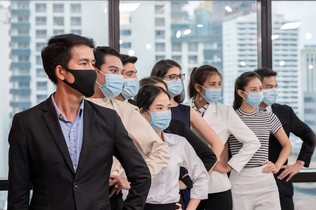 Row of multiethnic business group wearing face mask gesturing arm akimbo in new normal office while pandemic of coronavirus