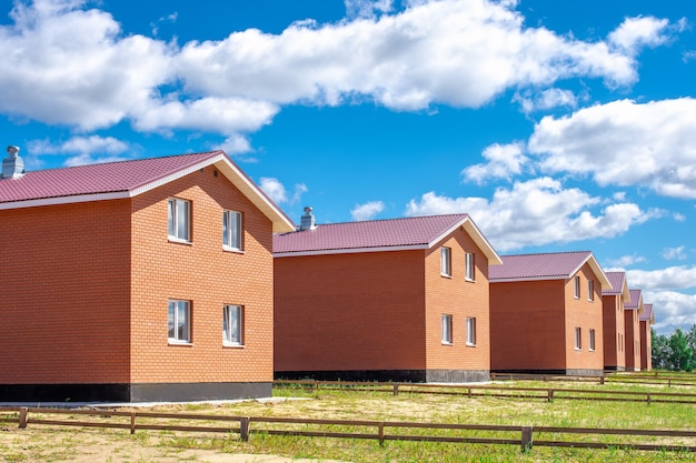 Row of new houses against a blue sky with beautiful clouds.