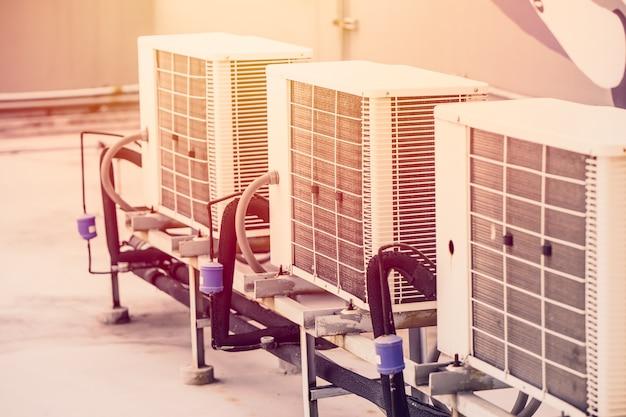 에어컨 압축기 장치의 행은 더운 여름 날씨와 함께 야외 사무실 건물을 설정합니다.