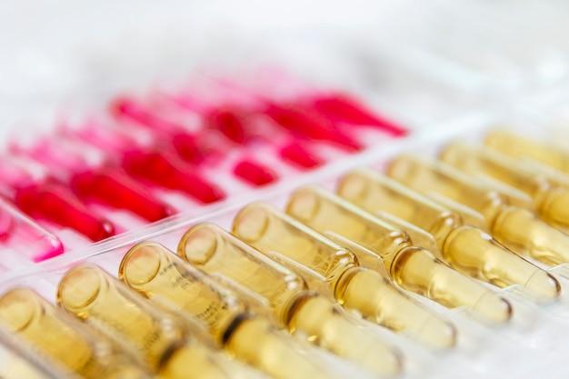 Ряд ампул с желтым лекарством. вакцина против вируса. крупный план.