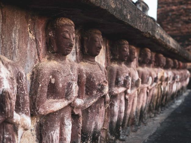 タイのユネスコ世界遺産に登録されているスコータイ歴史公園の境内にあるワットマハタート寺院の古い塔のふもとにある、古代の漆喰の列。