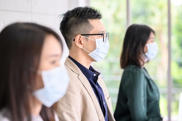 アジアの人々の列は、安全のために保護フェイスマスクを着用し、コロナウイルスのパンデミックから新しい通常のライフスタイルのために社会的な距離を保ちます。男に焦点を当てた