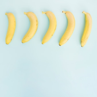Row of bananas on blue