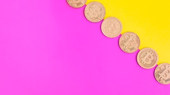 Row of bitcoins over pink and yellow dual background