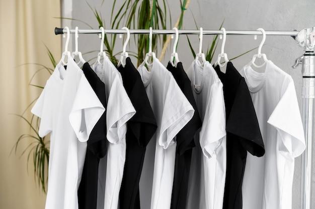랙에 매달려 있는 흑백 티셔츠 한 줄, 클로즈업