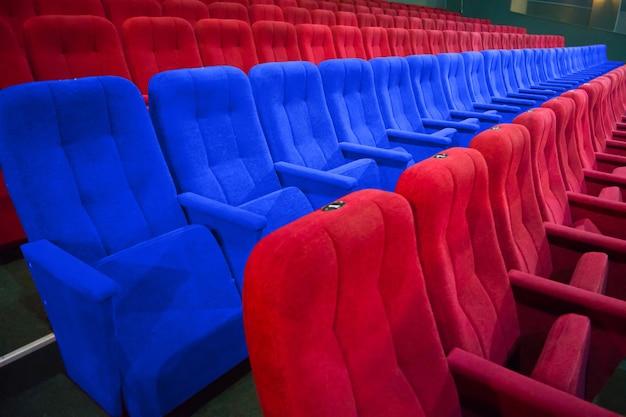 현대 영화의 빨간 좌석 사이에 파란 의자가 줄지어 있다
