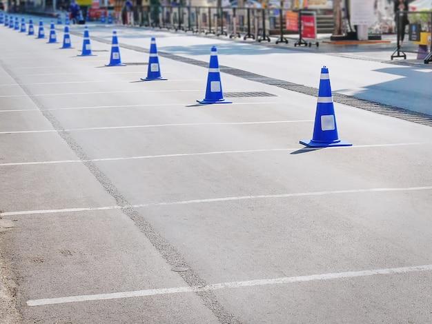 アスファルト通りの青いプラスチック製のトラフィックコーンの列