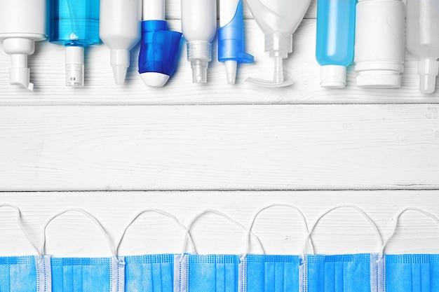Ряд бутылок с дезинфицирующими средствами для рук, жидким мылом и лекарственными препаратами по дереву