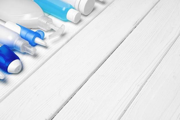 Ряд бутылок с дезинфицирующим средством для рук, жидким мылом и медицинскими препаратами на деревянном фоне
