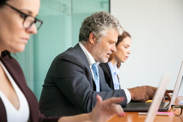 Ряд деловых людей, использующих компьютеры в офисе. сотрудники разного возраста набирают на клавиатуре ноутбука.