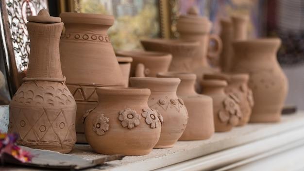 Ряд глиняных горшков на полке, размытый фон. детские поделки