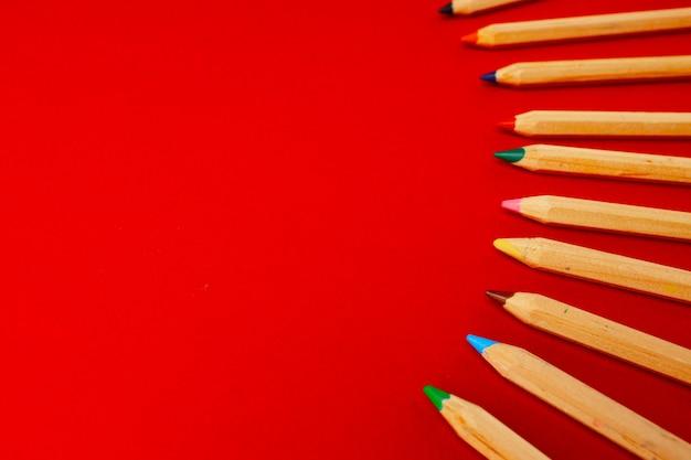 Ряд цветных деревянных карандашей на красном фоне вид сверху