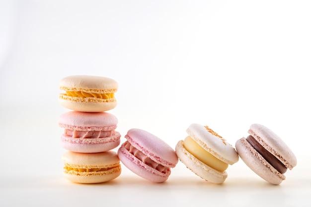 Ряд красочных пастельных французских миндальное печенье или миндальное печенье на белом и розовом фоне