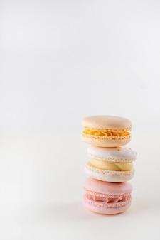 Ряд красочных пастельных французских миндальное печенье или миндальное печенье на белом фоне