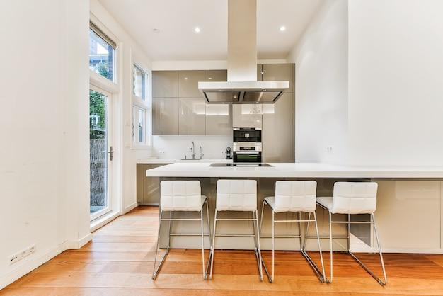 Ряд удобных стульев у прилавков под вытяжкой напротив шкафов и духовки на современной кухне