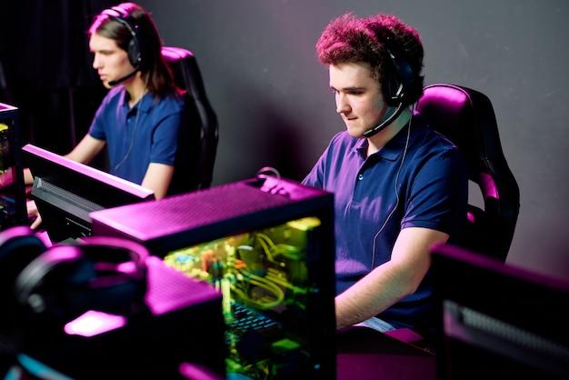 Ряд сосредоточенных молодых игроков в киберспорт в наушниках с микрофонами, сидящих перед компьютерами