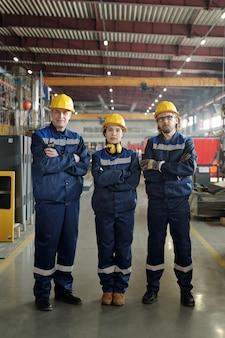 Ряд современных мужчин и женщин, работающих на крупном промышленном предприятии или фабрике, стоит перед камерой и смотрит на вас в мастерской