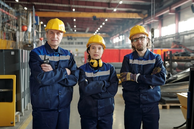 Ряд современных рабочих крупного промышленного предприятия или фабрики, стоящих перед камерой и смотрящих на вас, скрестив руки на груди