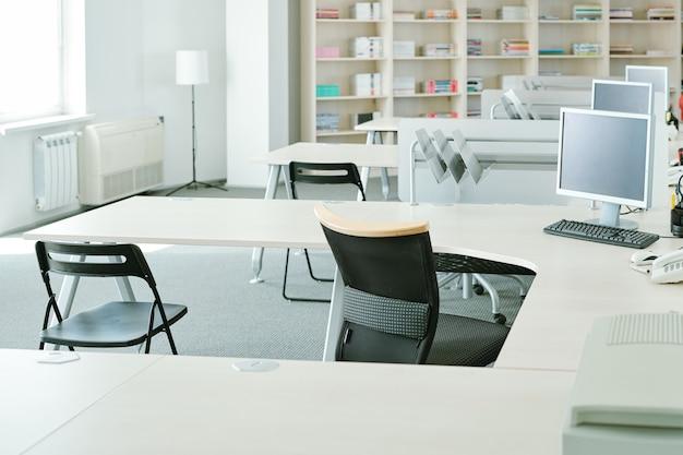 Ряд столов с компьютерными мониторами и стульями рядом с полками с документами, расходными материалами и лампой