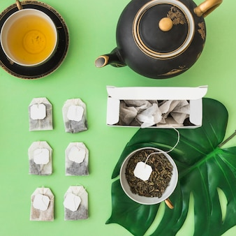 Row of different tea bags with tea cup and teapot on pale green backdrop