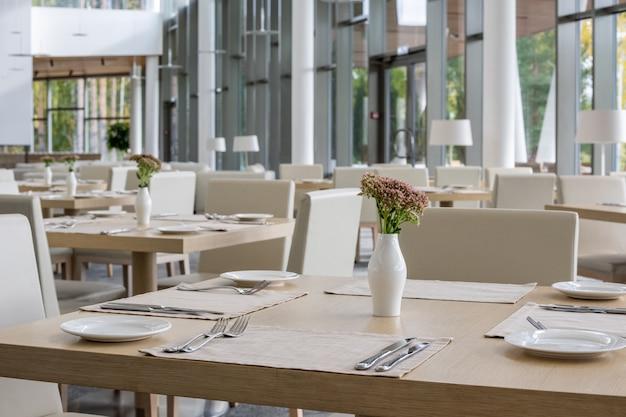 大規模なビジネスセンターの現代的な豪華なレストラン内の花とプレート、ナプキン、花瓶を添えたディナーテーブルの列