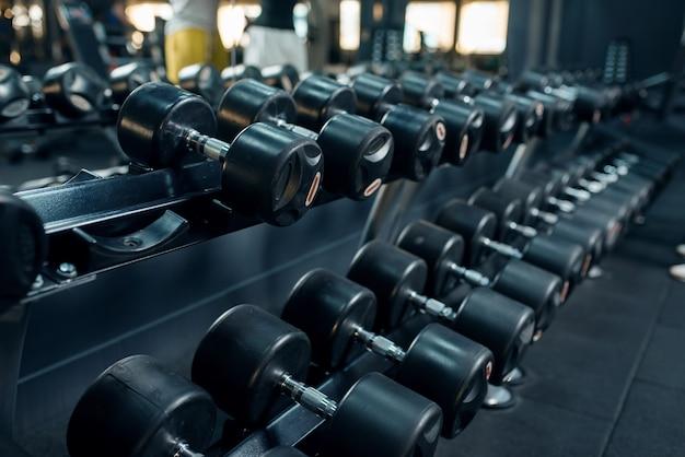 ジムのクローズアップでダンベルの行。フィットネスエクササイズ用の機器、スポーツトレーニング用のヘビーウェイト