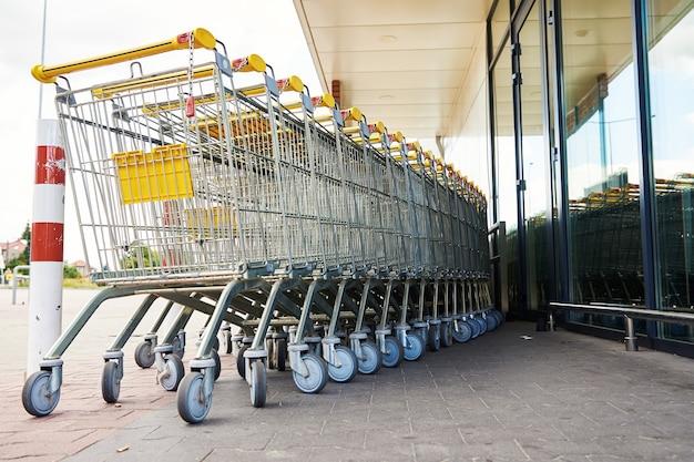 Ряд пустой корзины покупок возле магазина крупным планом