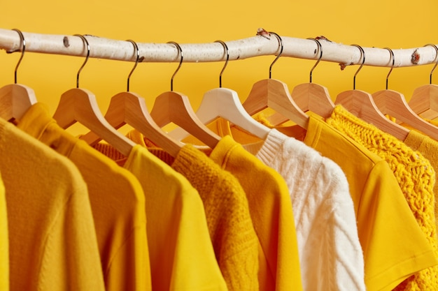 黄色の背景に木製のラックにぶら下がっているファッショナブルな服の列。冬の衣料品コレクションでは、白いニットのセーターが際立っています。