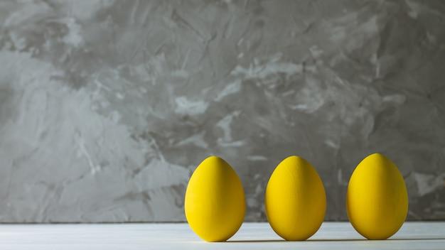 Ряд из пяти ярко-желтых пасхальных яиц, стоящих на белой деревянной поверхности на серой бетонной поверхности