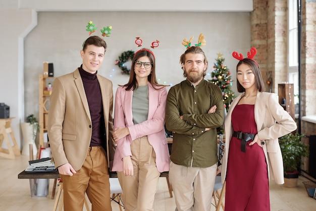 現代のオフィスでカメラの前に立っているスマートカジュアルウェアとクリスマスヘッドバンドの4人の若い異文化ホワイトカラー労働者の列