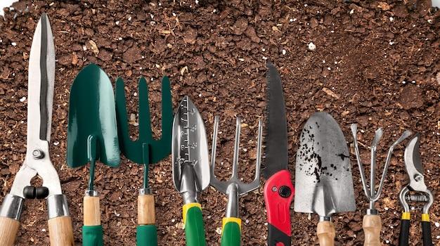 Ряд садовых инструментов на фоне почвы