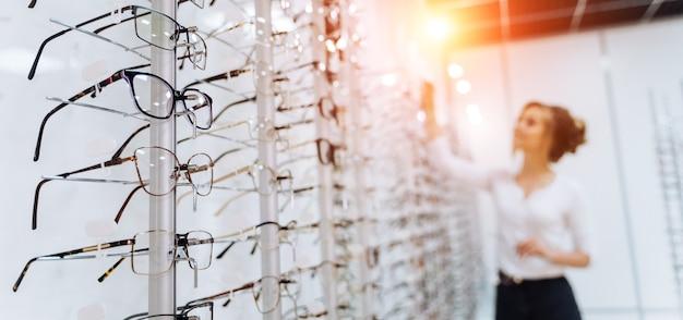 안경점에서 안경의 행입니다. 안경점. 안경점에서 안경을 쓰고 서십시오. 여자는 안경을 선택합니다. 안경 제시