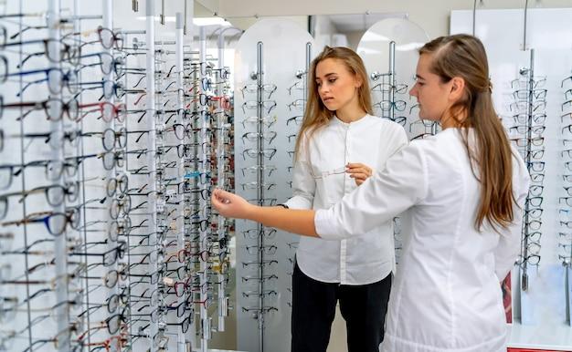 Ряд очков в оптике. магазин очков. стенд с очками в магазине оптики. женщина-офтальмолог дает очки клиентке.