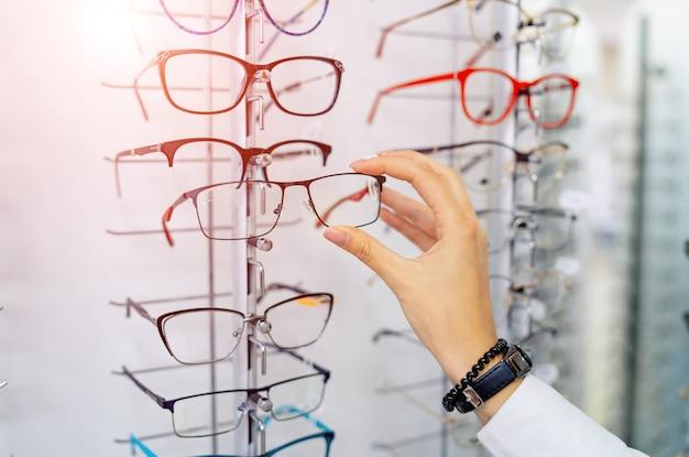 眼鏡店で眼鏡の行。眼鏡店。光学系の店で眼鏡をかけて立ちます。女性の手は眼鏡を選択します。視力矯正。