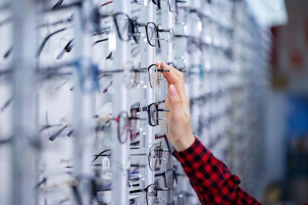 Ряд очков в оптике. магазин очков. стенд с очками в магазине оптики. женская рука показывает очки. представляем очки. крупным планом