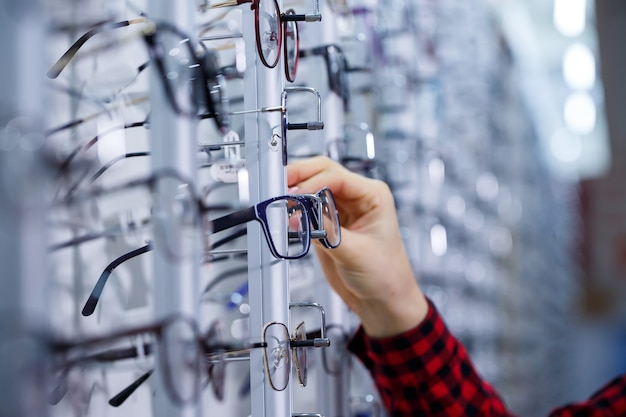 Ряд очков в оптике. магазин очков. стенд с очками в магазине оптики. женская рука показывает очки