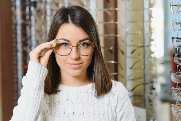 Ряд очков в оптике. магазин очков. женщина выбирает очки. коррекция зрения.
