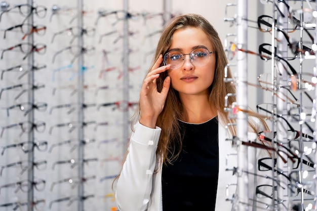 안경점에서 안경의 행입니다. 안경에 여자입니다. 안경점에서 안경을 쓰고 서십시오. 현대적인 안과 매장에서 안경을 진열하세요. 확대.