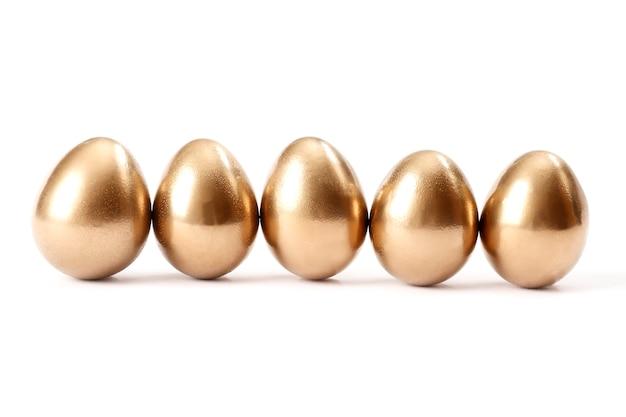 흰색 배경에 고립 된 황금 계란의 행입니다.