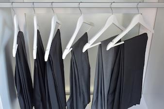 Row of gray and black pants hangs in wardrobe at home