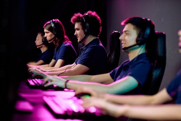 コンピューターの画面の前にある黒い革張りのアームチェアに座って、クラブでeスポーツゲームをプレイしているカジュアルウェアとヘッドセットの男たちの列